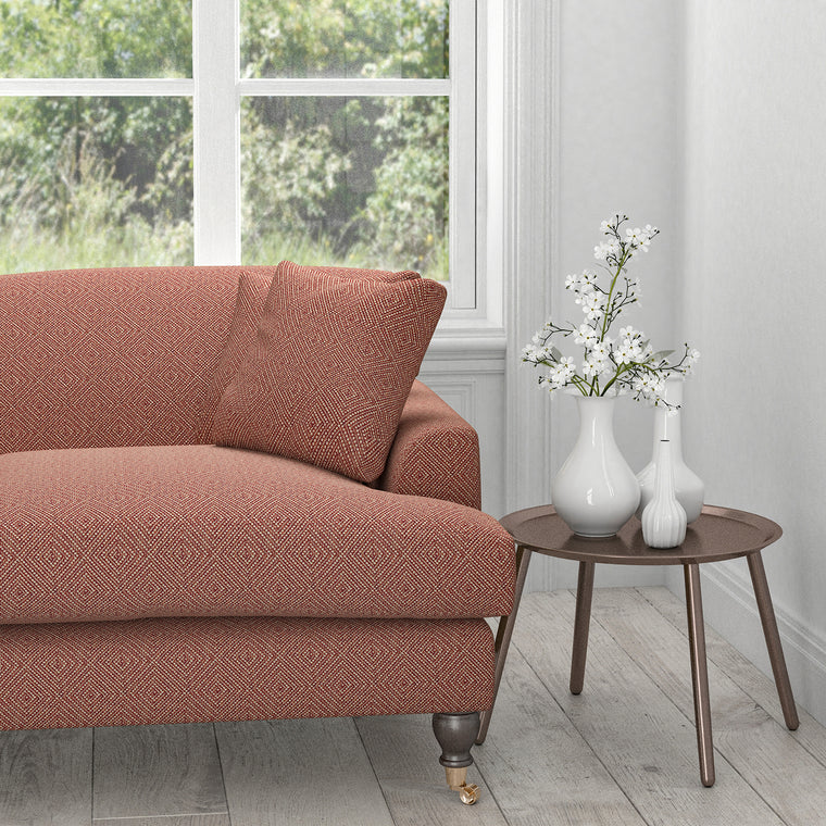 Sofa in an burnt orange fabric with a neutral geometric woven design