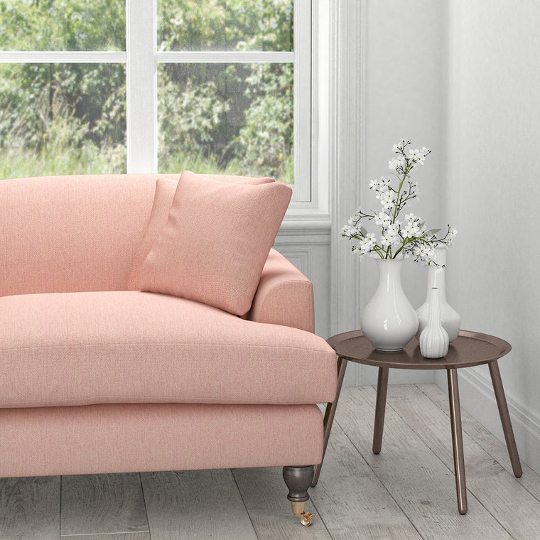 Sofa in a light pink upholstery fabric with a light neutral woven geometric design