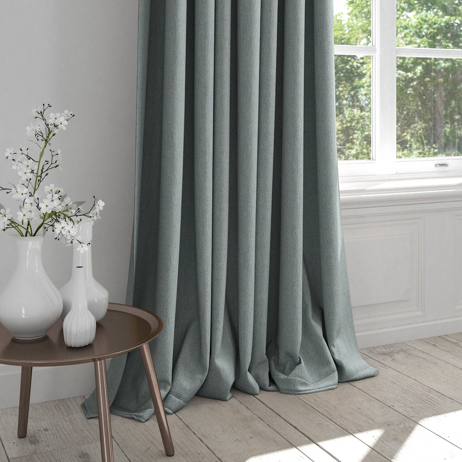 Curtains in a light blue fabric with a light neutral woven geometric design