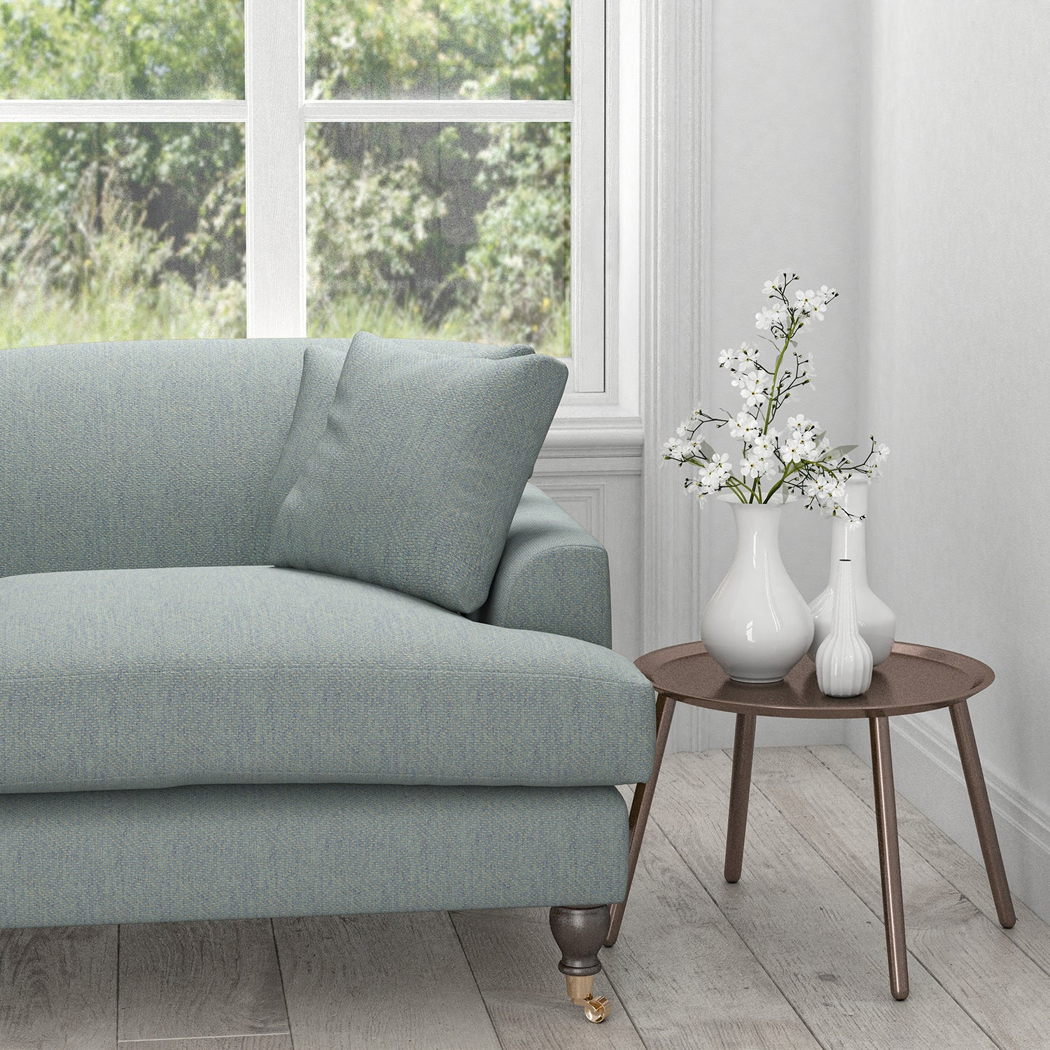 Sofa upholstered in a light blue fabric with a neutral woven design