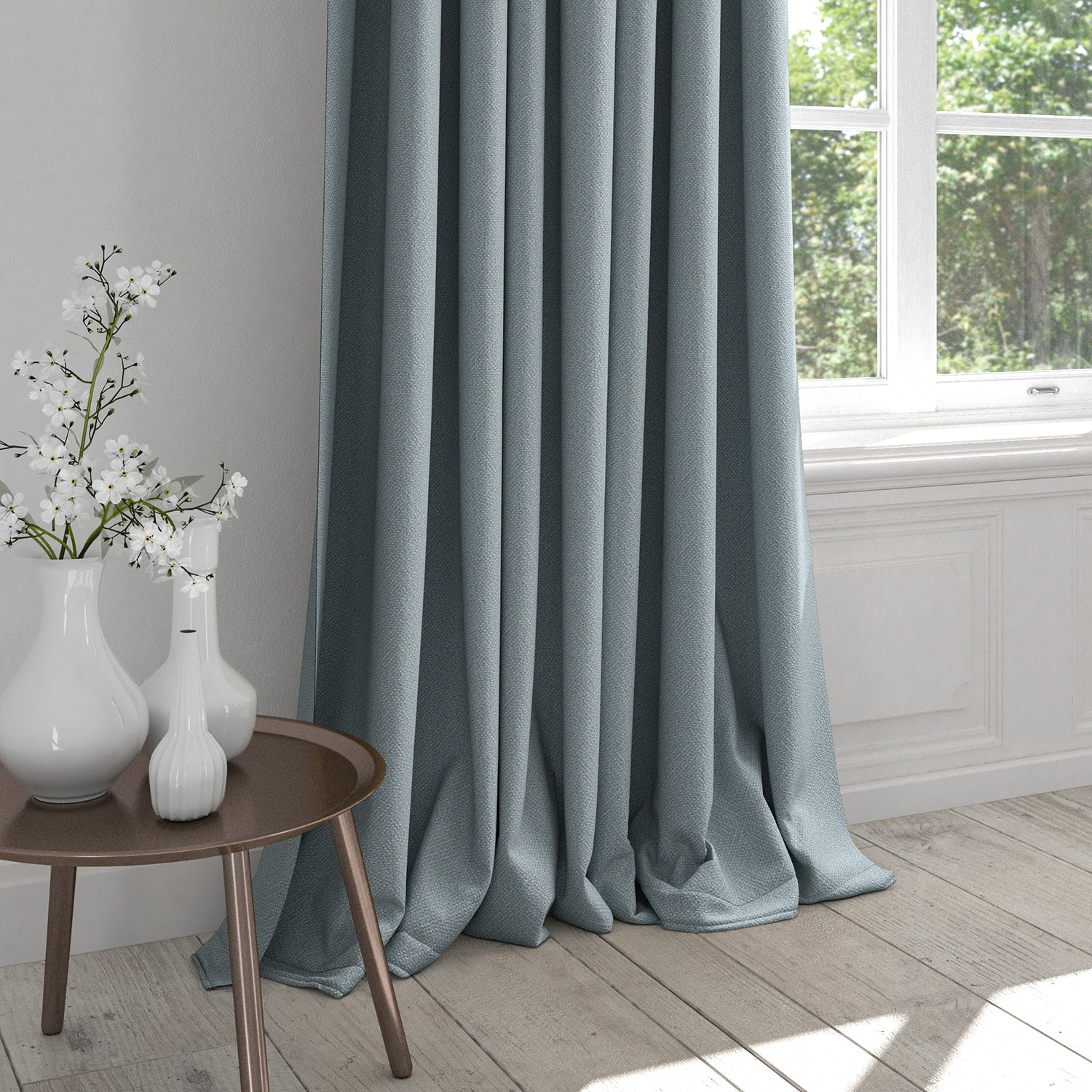 Curtain in a light blue fabric with light woven geometric design