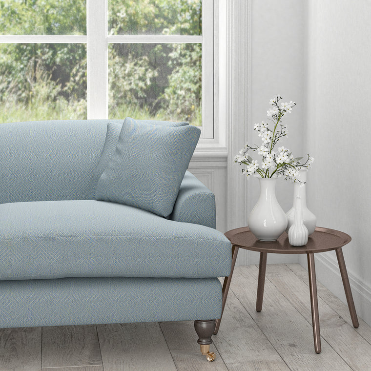 Sofa in a light blue fabric with neutral woven geometric design