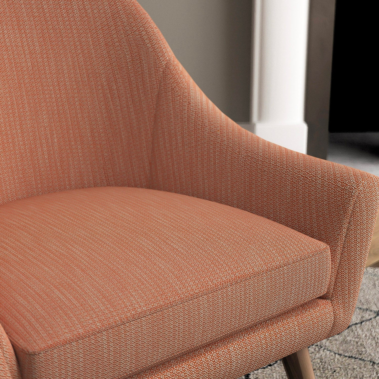 Chair with a orange and neutral upholstery fabric with a small diamond weave fabric