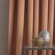 Curtain in a orange and neutral weave fabric with a small diamond design and a stain resistant finish