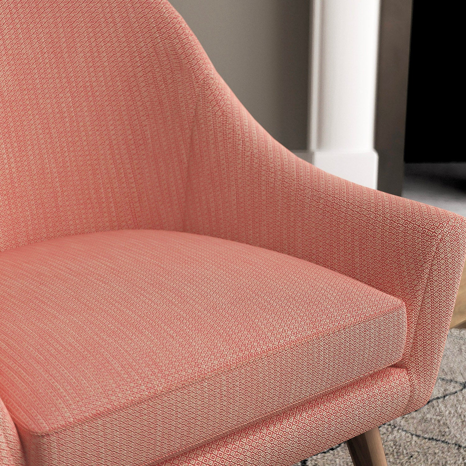 Chair with a bright pink and neutral upholstery fabric with a small diamond weave fabric