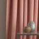 Curtain in a bright pink and neutral weave fabric with a small diamond design and a stain resistant finish