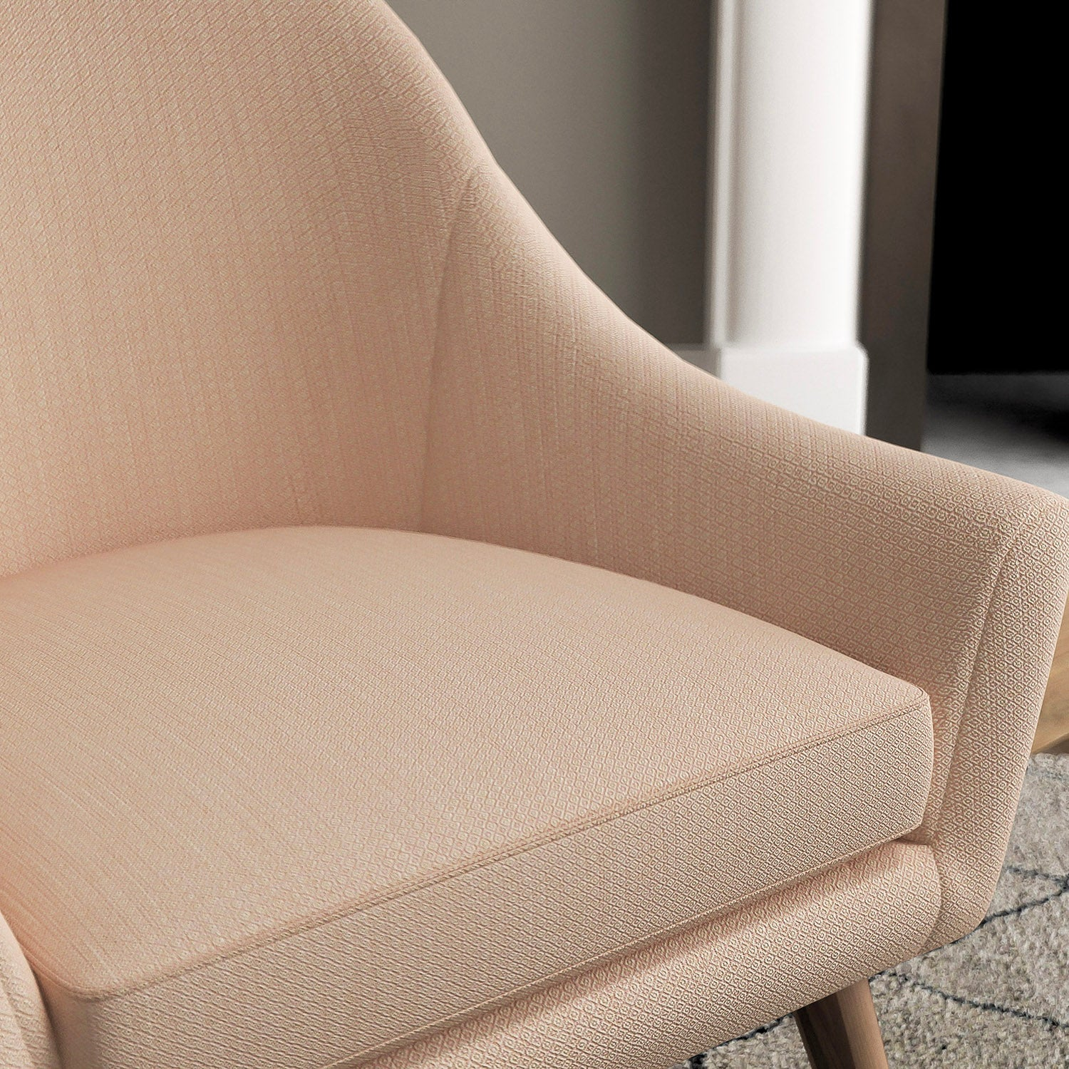 Chair with a blush pink and neutral upholstery fabric with a small diamond weave fabric