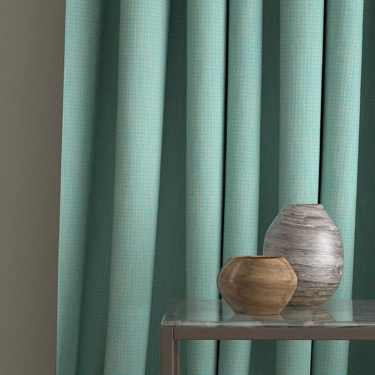 Curtain in a turquoise and neutral weave fabric with a small diamond design and a stain resistant finish