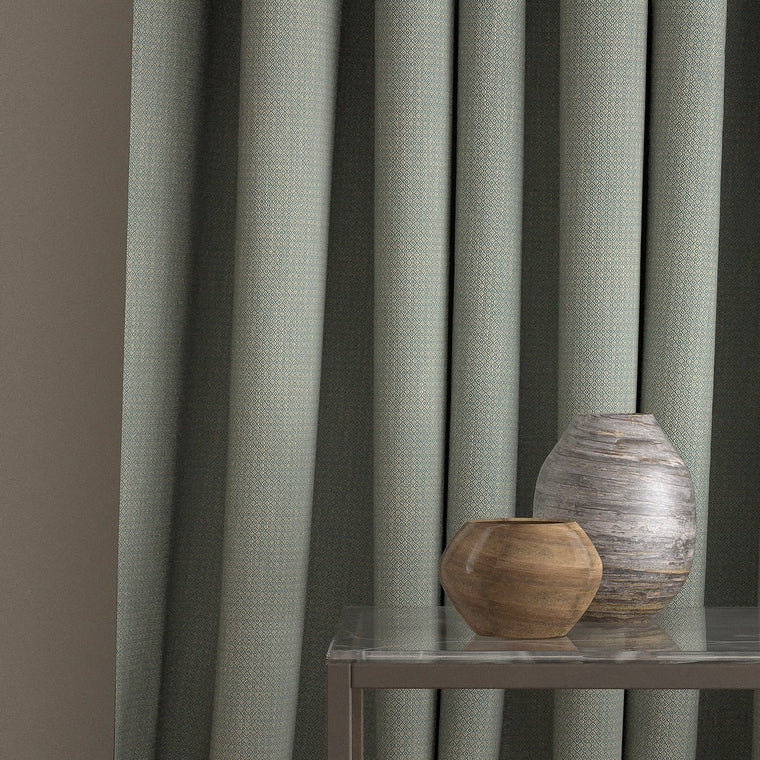 Curtain in a blue and neutral weave fabric with a small diamond design and a stain resistant finish