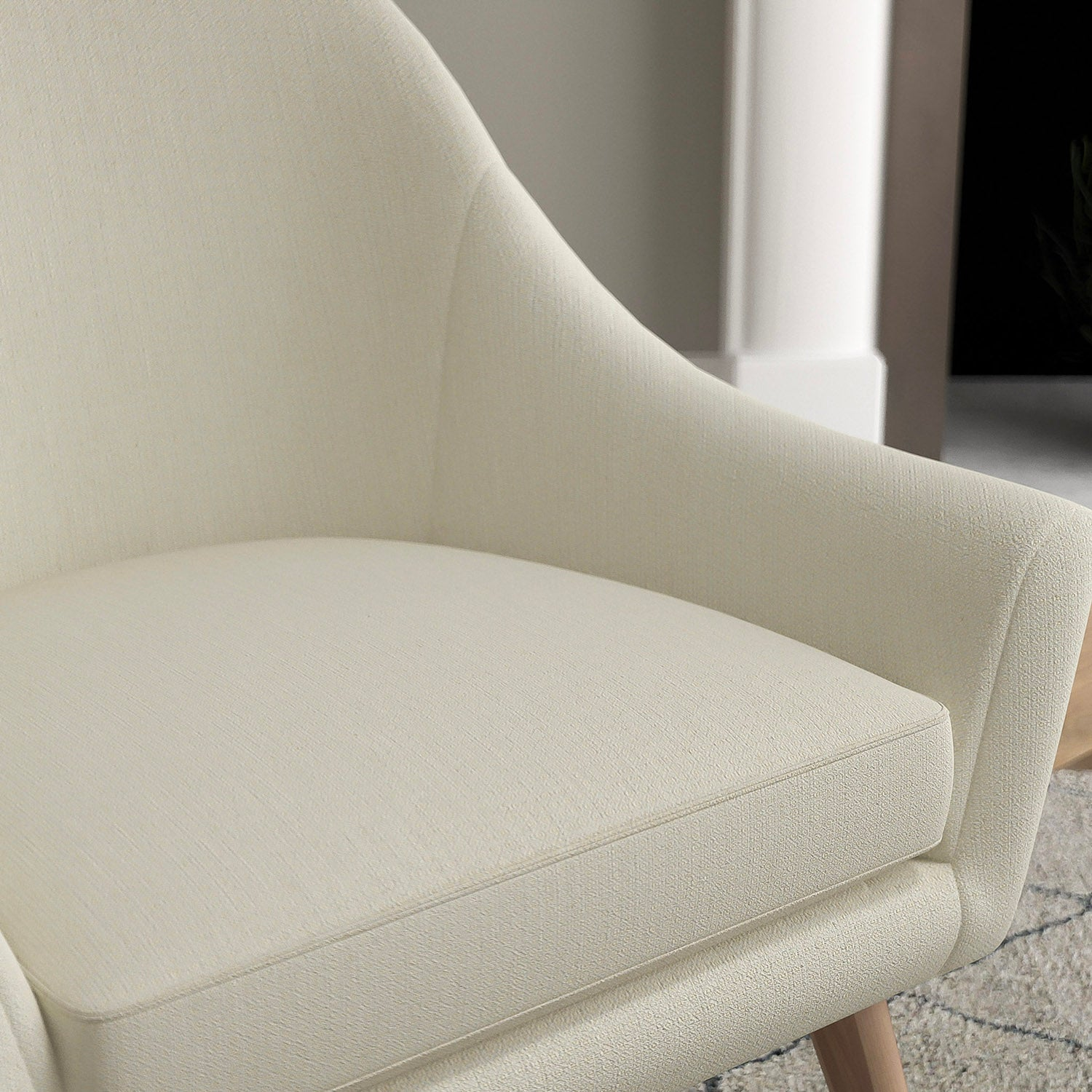 Chair with a light grey and neutral upholstery fabric with a small diamond weave fabric