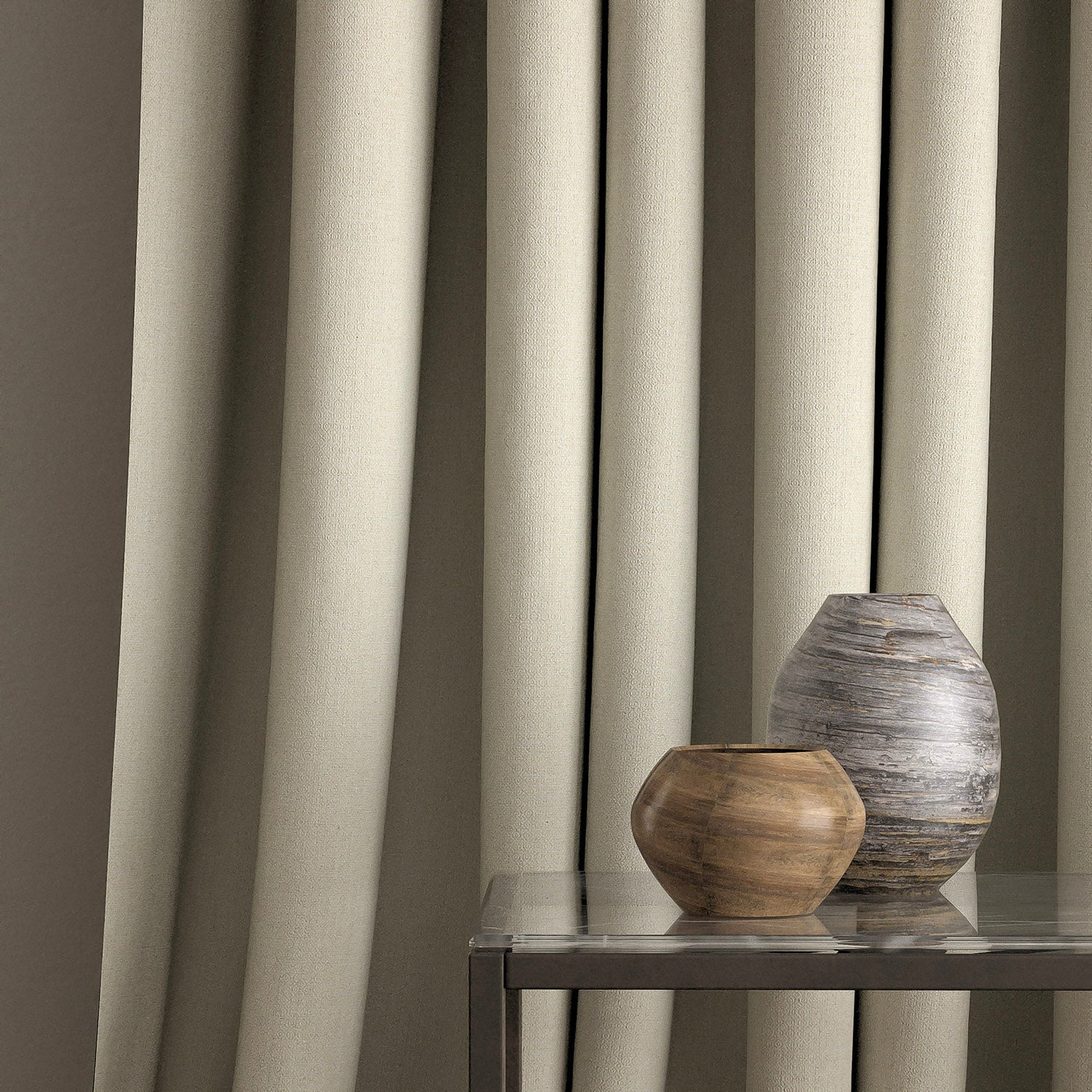 Curtain in a light grey and neutral weave fabric with a small diamond design and a stain resistant finish