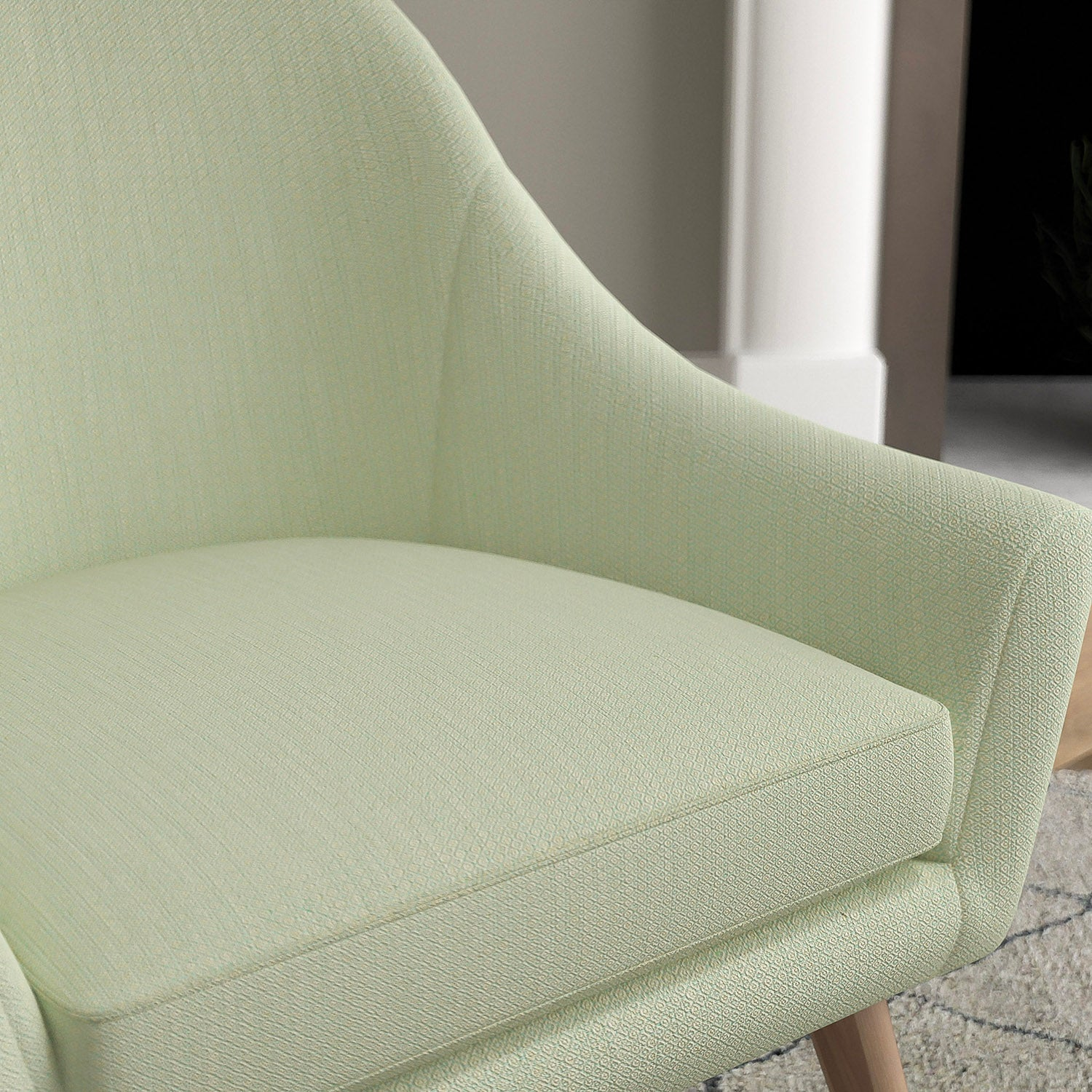 Chair with a mint green and neutral upholstery fabric with a small diamond weave fabric