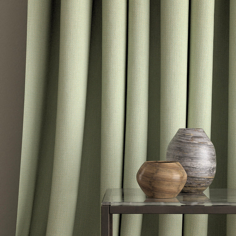 Curtain in a mint green and neutral weave fabric with a small diamond design and a stain resistant finish