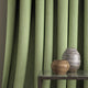 Curtain in a green and neutral weave fabric with a small diamond design and a stain resistant finish