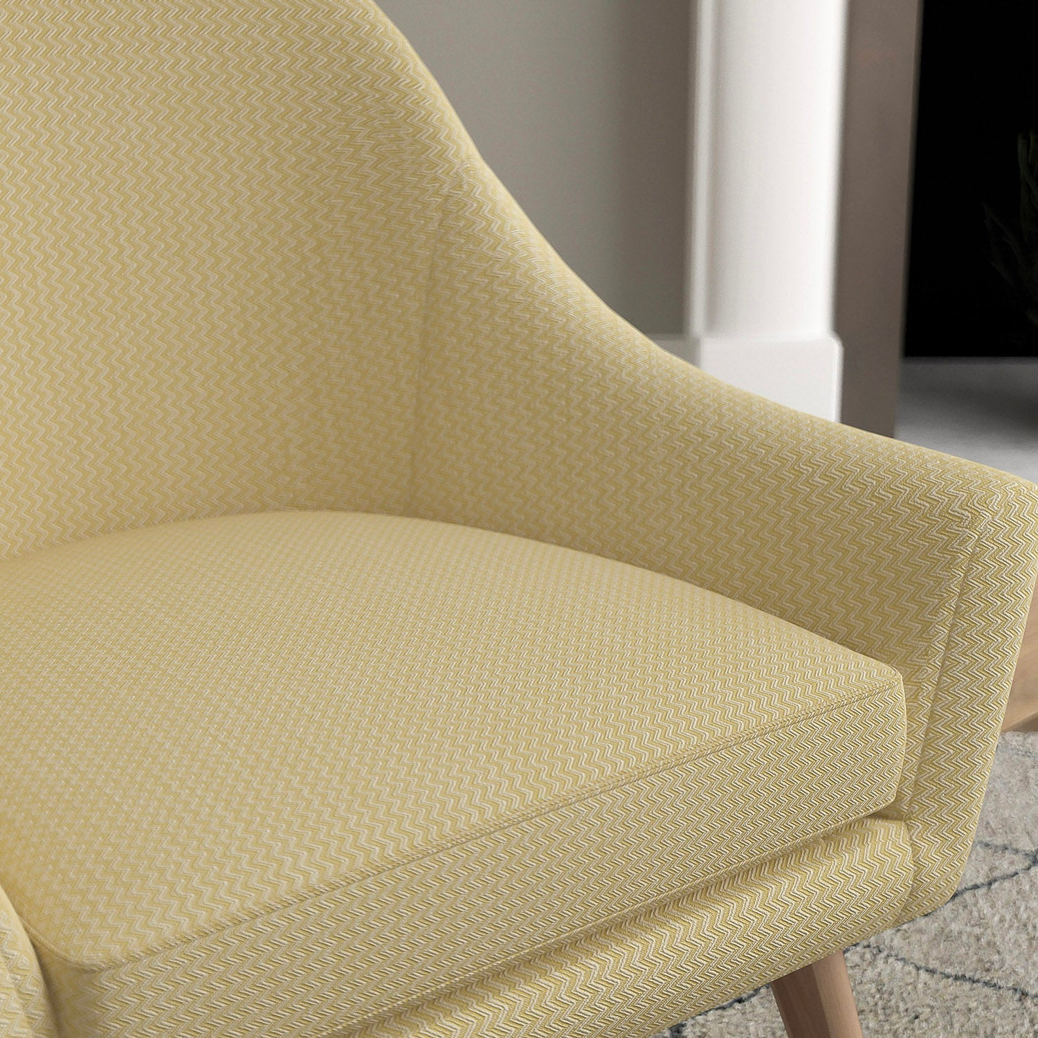 Chair with a bright yellow and neutral upholstery fabric with a chevron weave fabric