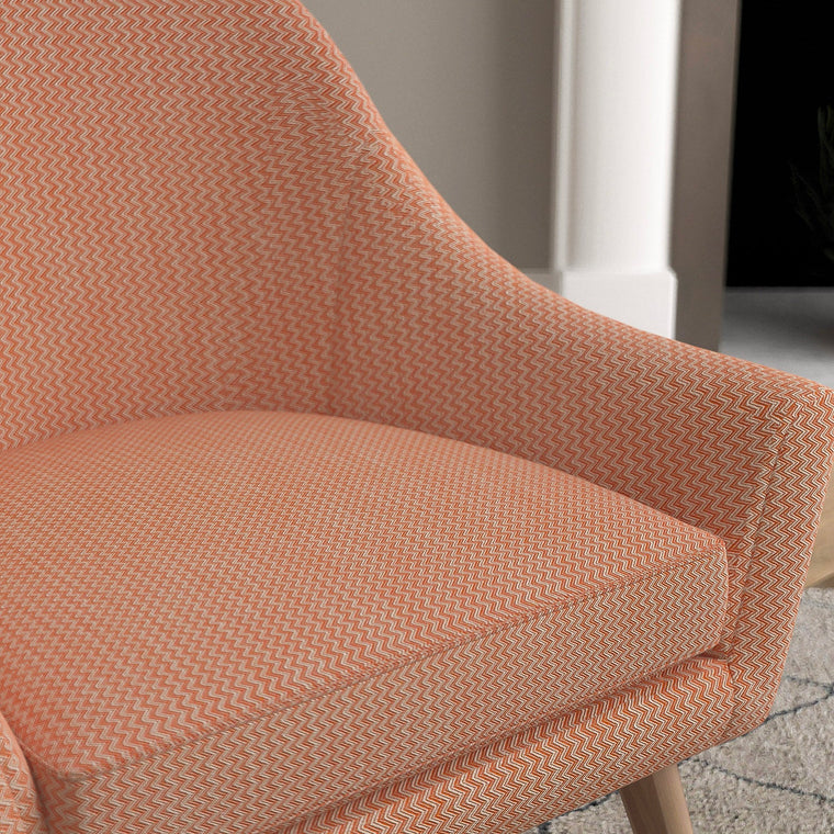 Chair with a orange and neutral upholstery fabric with a chevron weave fabric