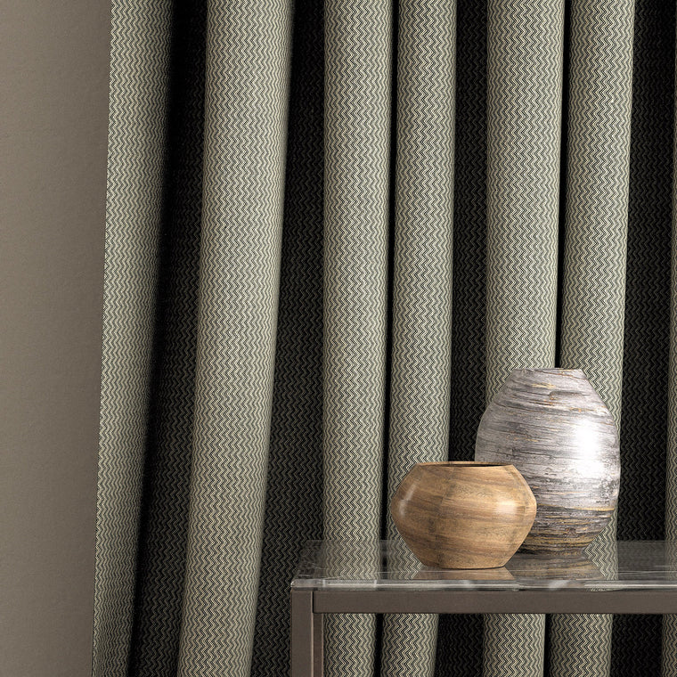 Curtain in a dark grey and neutral chevron weave fabric with a stain resistant finish