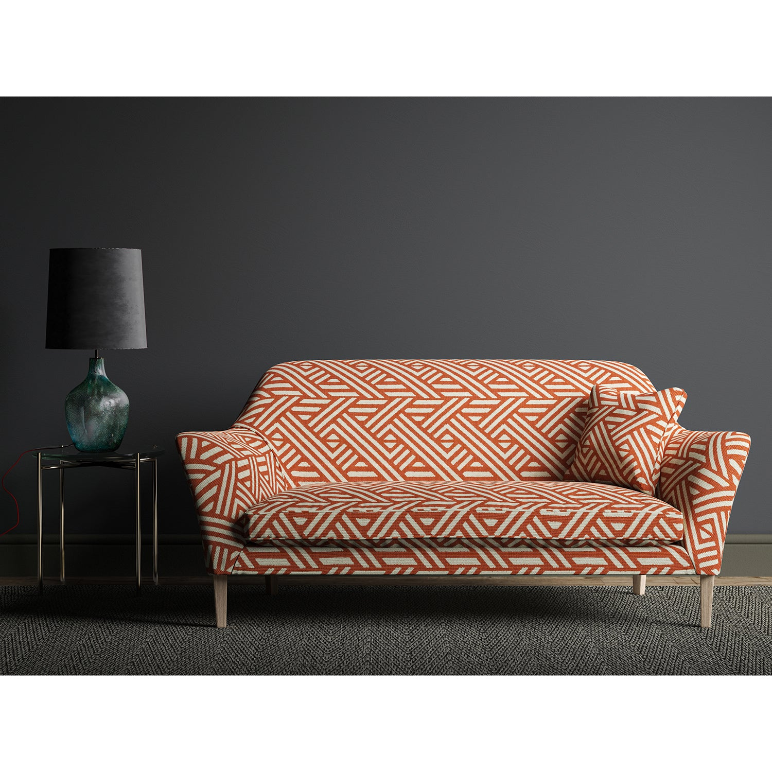 Sofa upholstered in a large scale geometric print with orange and white colours