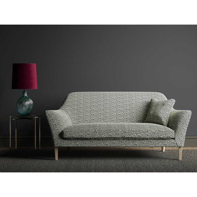 Sofa upholstered in a monochrome wavy geometric weave fabric.
