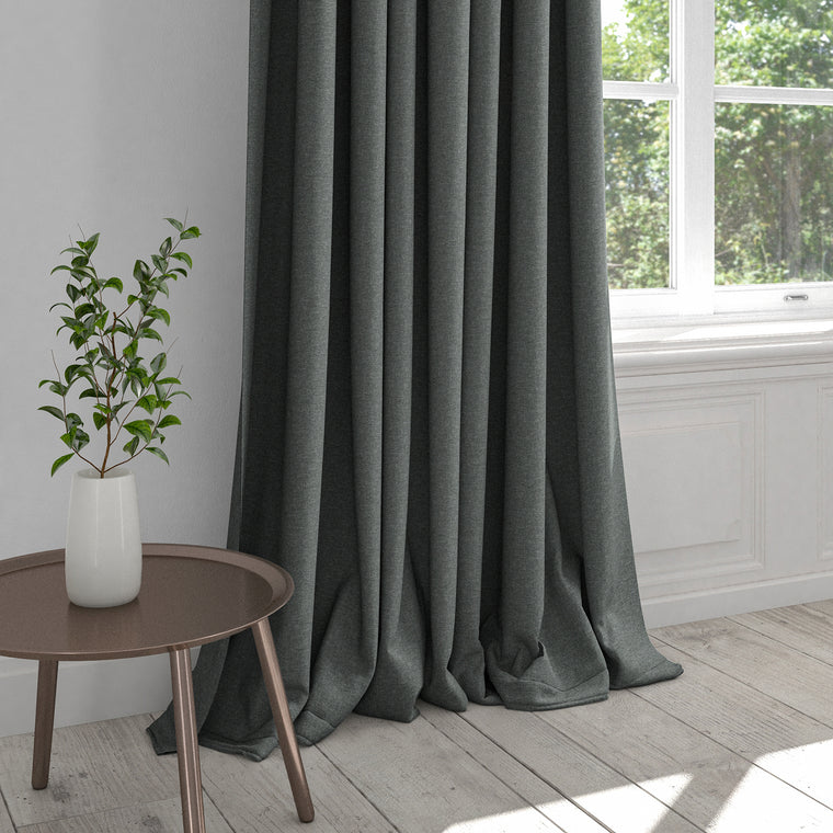 Curtain upholstered in a dark indigo blue plain cotton fabric