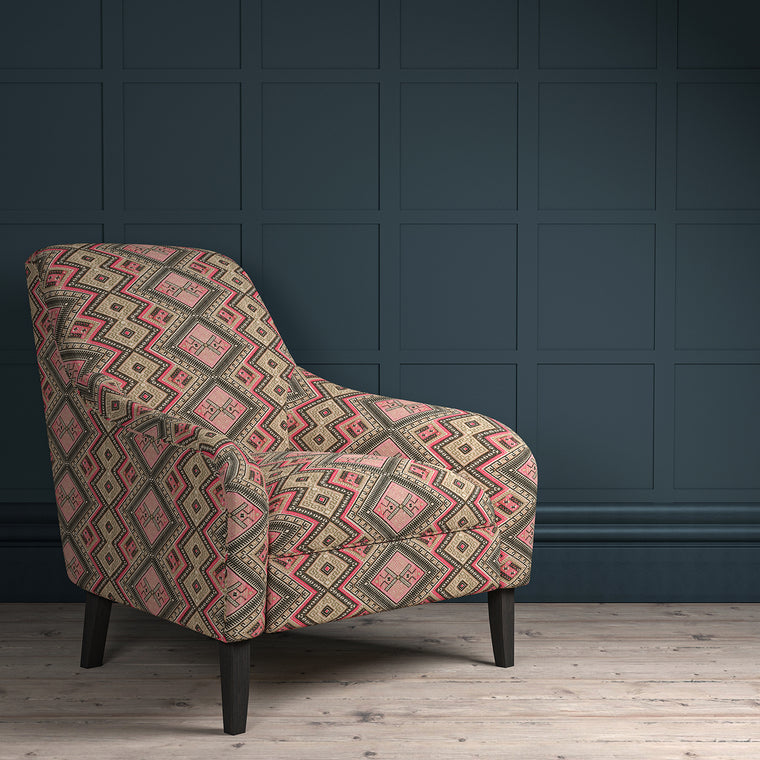 Chair upholstered in a pink coloured geometric upholstery fabric