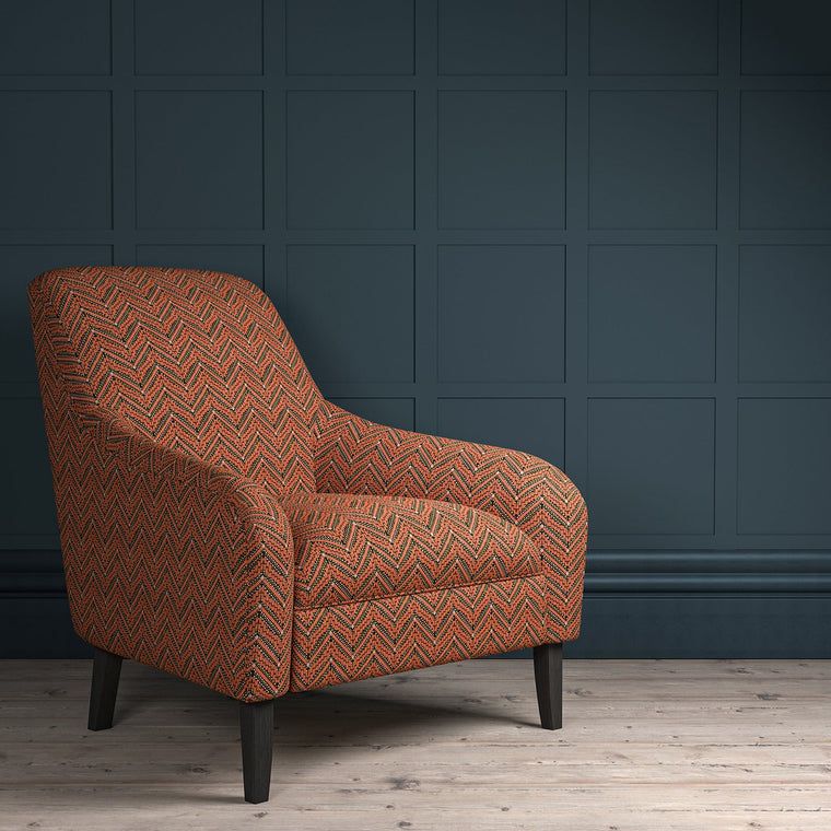 Chair upholstered in a dark orange coloured zig zag geometric upholstery fabric