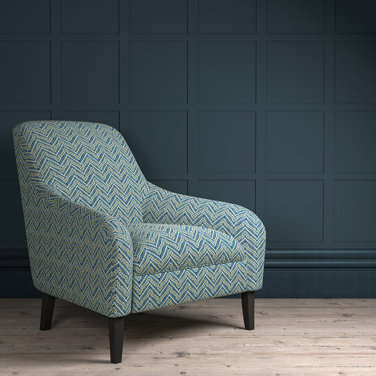 Chair upholstered in a dark blue coloured zig zag geometric upholstery fabric