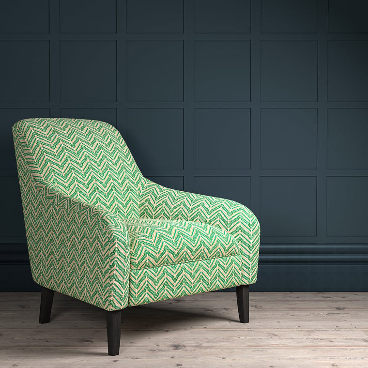 Chair upholstered in a bright green coloured zig zag geometric upholstery fabric