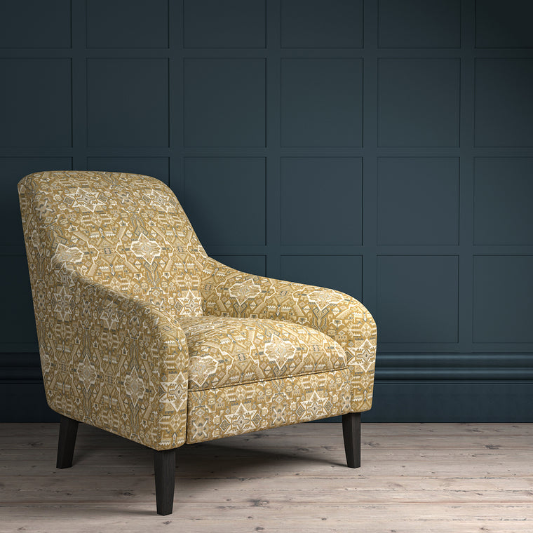 Chair upholstered in a dark neutral coloured large scale geometric upholstery fabric