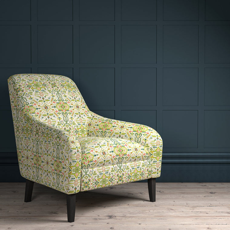Chair upholstered in a green and light neutral coloured large scale geometric upholstery fabric