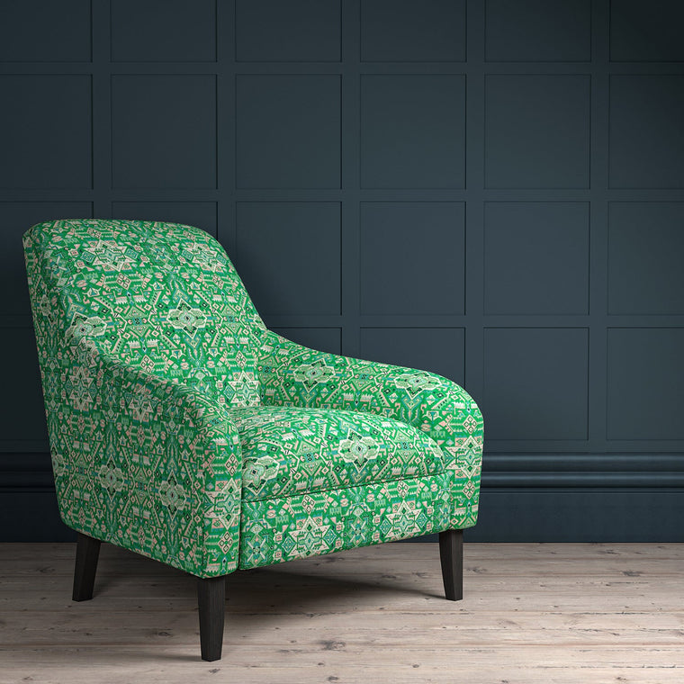 Chair upholstered in a green and pink coloured large scale geometric upholstery fabric