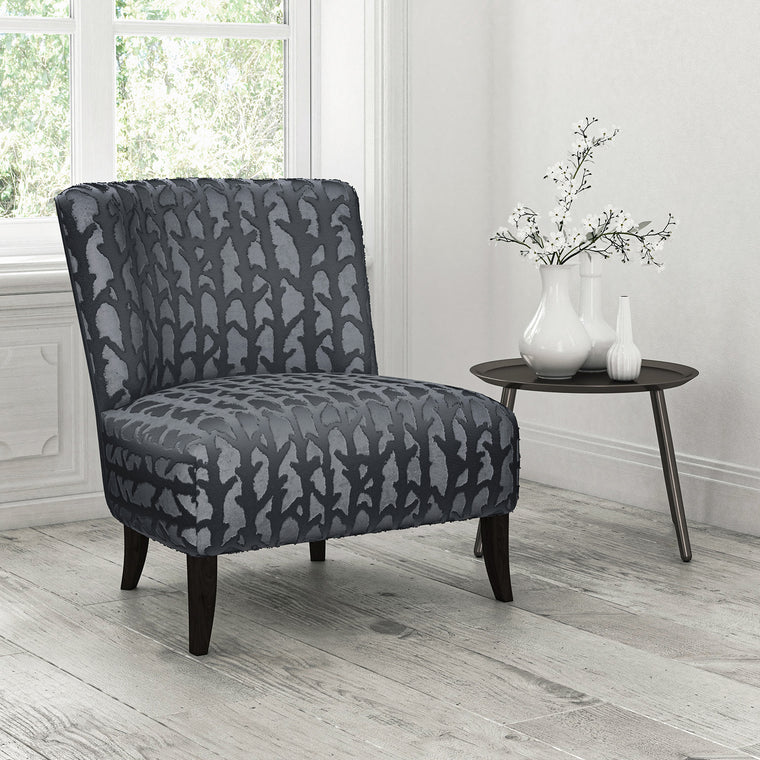 Chair upholstered in a blue velvet upholstery fabric with abstract branch design