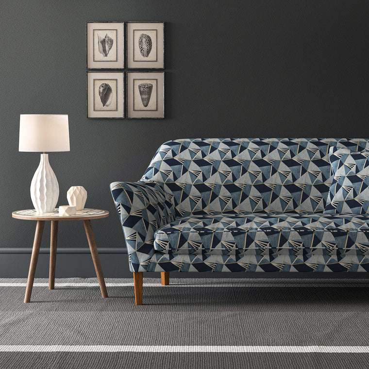 Sofa upholstered in a blue velvet fabric with geometric design and stain resistant finish
