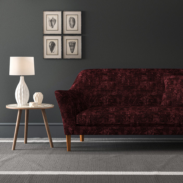 Velvet sofa upholstered in a dark red velvet fabric with a carpet design and a stain resistant finish