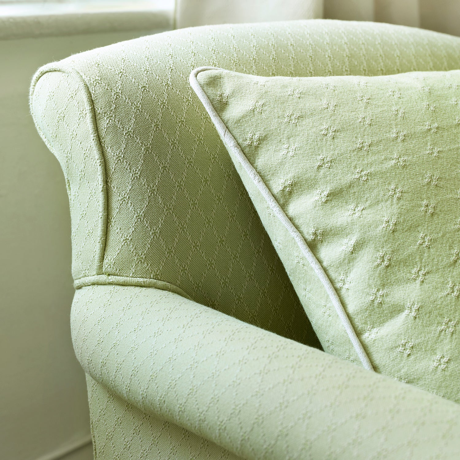 Armchair upholstered in a light green classic upholstery fabric with stain resistant finish