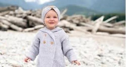 little girl in grey coat and headband standing on the beach