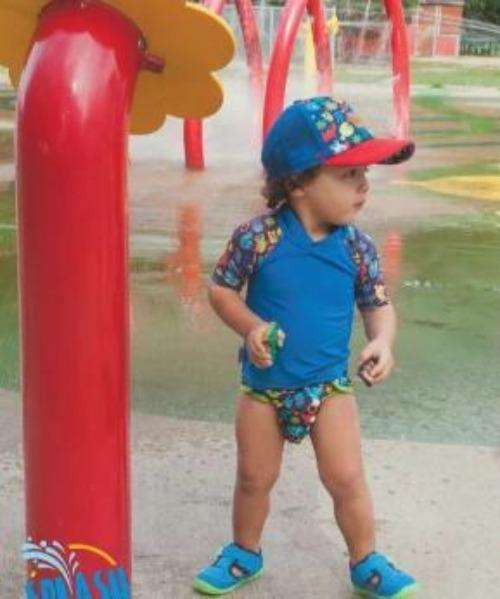 little boy wearing matching blue tee and diaper at water park- Bumbini Cloth Diaper Company