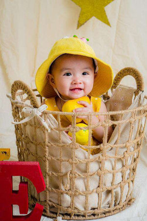 baby wearing yellow rain suit and sitting in laundry basket - Bumbini Cloth Diaper Company