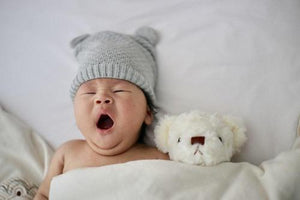 baby sleeping with grey hat and teddy bear beside them- Bumbini Cloth Diaper Company