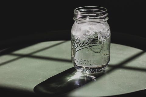 A glass mason jar filled with water and ice - remember to hydrate!