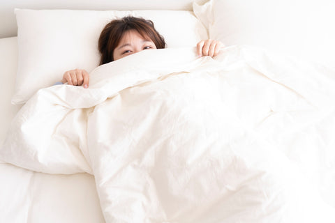 A woman laying on a white bed. She's pulling her white bed covers up to her face.