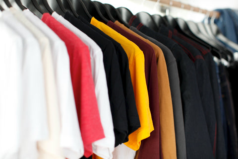 A  full clothing rack with garments that range from light to dark colors