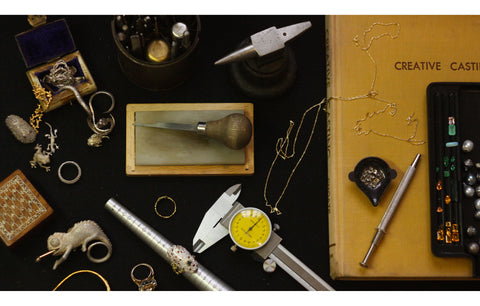 Jewellery tool and rings laid out on a black table cloth, with a book about casting techniques and a tray of gemstones