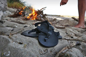 shamma sandals running shoes on rock with campfire in background