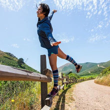 Load image into Gallery viewer, lily trotters calf sleeves striped colors woman balancing on fence