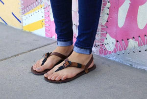 shamma sandals running woman standing next to mural in sandals