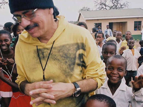 Santana smiling while surrounded by a classroom full of children overseas