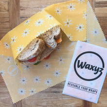 Load image into Gallery viewer, A sandwich waxyz wrap in yellow daisy design. A reusable alternative to cling film.