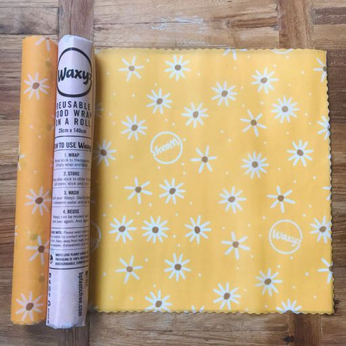 Yellow daisy reusable waxyz wrap on a roll. A reusable alternative to cling film to be cut to your own size.