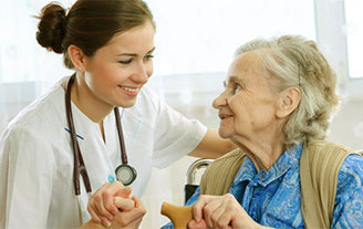 Caregiver smiling at an elderly woman